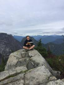 Cameron reading Mark Vellend's 'The Theory of Community Ecology' book on the top of a mountain.